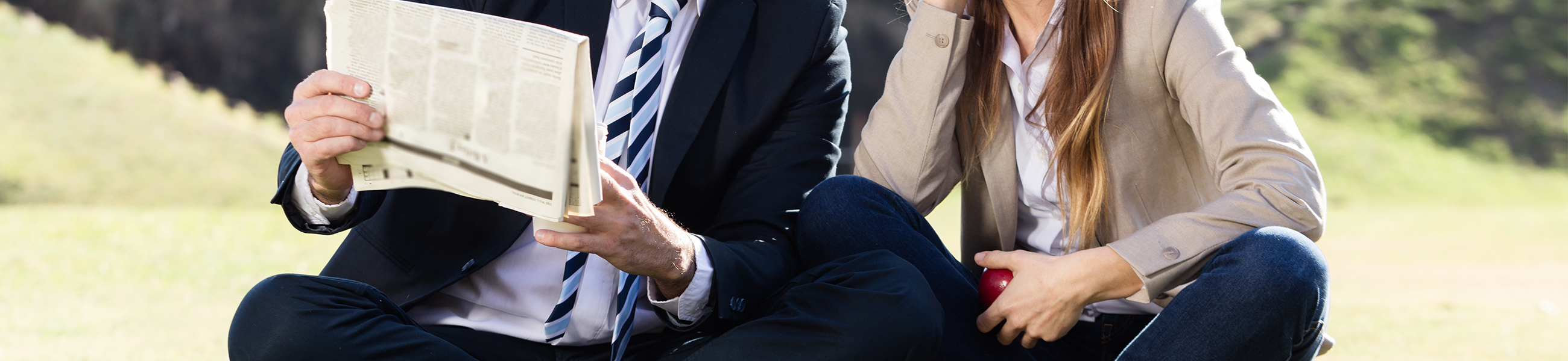 A close-up shot of two people sitting outside on the grass. One is reading a newspaper and the other one is holding an apple. They are only depicted from the shoulders down.