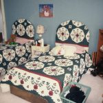 A small bedroom with two single beds in it. There are many toys and books in the room.