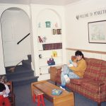 A living room. A woman is sitting on a couch. She is feeding a baby with a bottle. On the left there is a little girl playing with a toy.